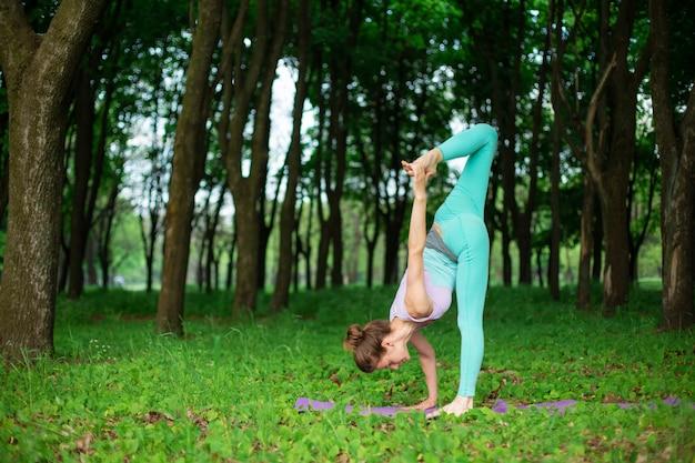 Garota jovem esportes pratica ioga em uma floresta de verão verde sair, postura de yoga assans. meditação e unidade com a natureza