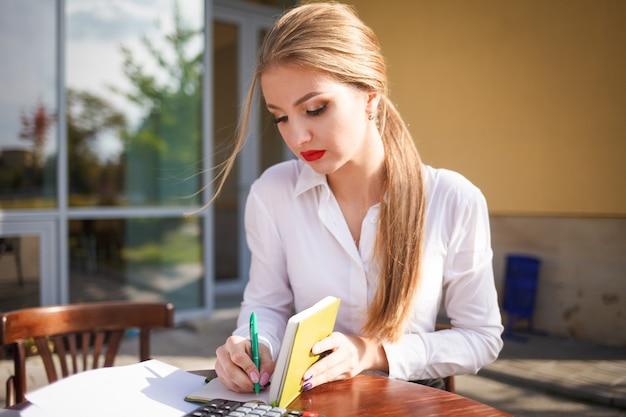 Garota jovem estudante escreve um diário.