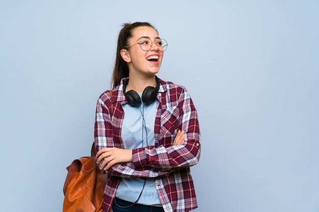 Garota jovem estudante sobre fundo azul