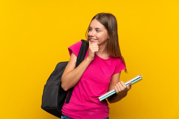 Garota jovem estudante sobre parede amarela isolada, pensando uma idéia e olhando de lado