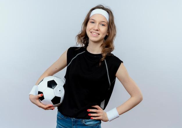Garota jovem fitness em roupa esportiva preta com tiara segurando uma bola de futebol, sorrindo confiante em pé sobre uma parede branca