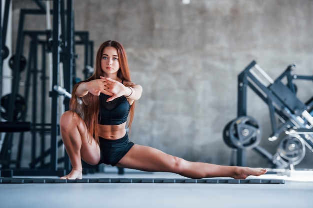 Garota jovem fitness em roupas esportivas pretas, fazendo exercícios de ioga no ginásio.