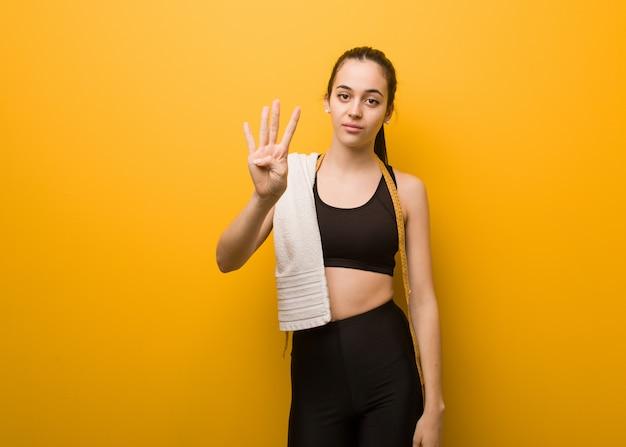 Garota jovem fitness mostrando o número quatro