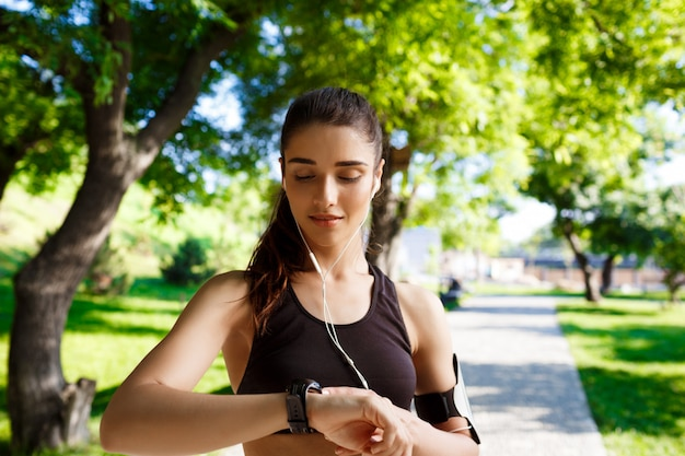 Garota jovem fitness olhando para o relógio