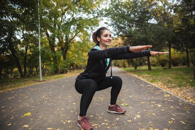 Garota jovem fitness sorridente fazendo exercícios no parque, agachada
