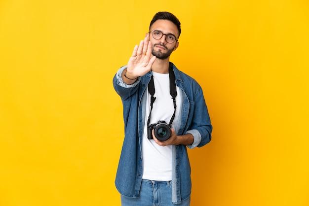 Garota jovem fotógrafa isolada em um fundo amarelo fazendo gesto de pare