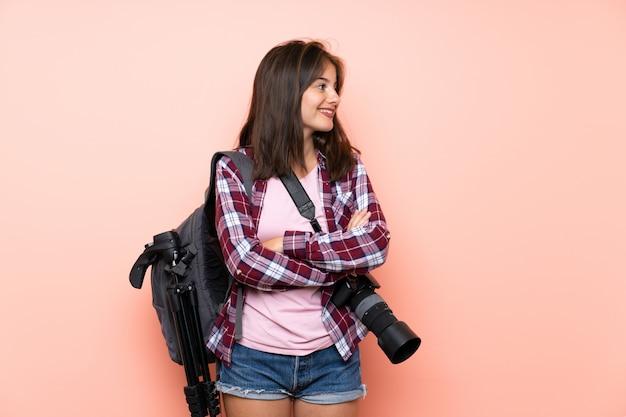 Garota jovem fotógrafo sobre parede rosa isolada, olhando para o lado