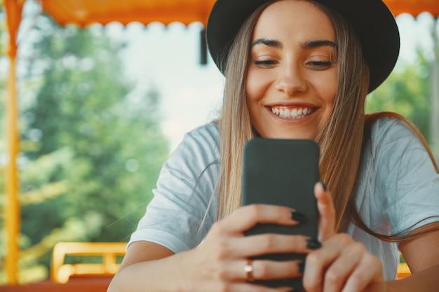 Garota jovem hippie no chapéu da moda segurando o smartphone nas mãos
