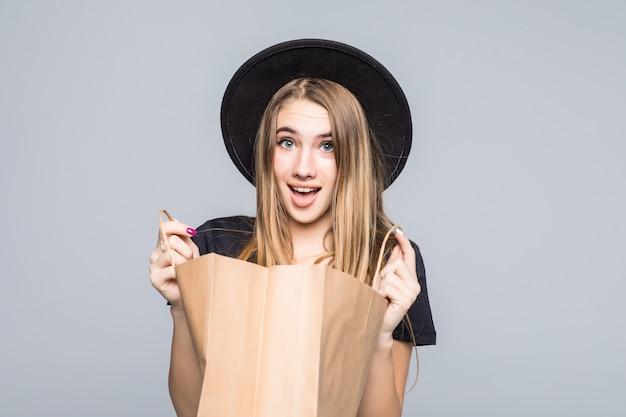 Garota jovem hippie vestida com uma camiseta preta e calças de couro segurando bolsas de artesanato em branco com alças isoladas em branco