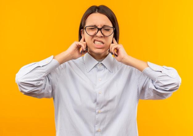 Garota jovem irritada do call center usando óculos, colocando os dedos nas orelhas com os olhos fechados, isolado em laranja
