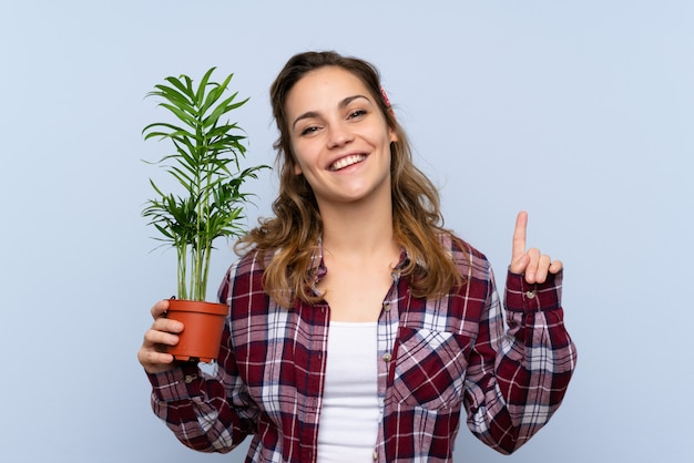 Garota jovem jardineiro loira segurando uma planta apontando para cima uma ótima idéia