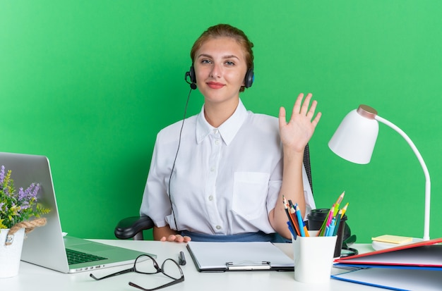 Garota jovem loira de call center satisfeita usando fone de ouvido, sentada na mesa com ferramentas de trabalho, fazendo gestos de olá