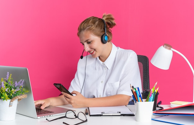 Garota jovem loira sorridente de call center usando fone de ouvido, sentada na mesa com ferramentas de trabalho, usando laptop e telefone celular isolado na parede rosa