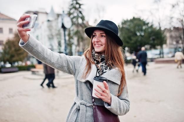 Garota jovem modelo em um casaco cinza e chapéu preto com bolsa de couro nos ombros fica com copo plástico de café