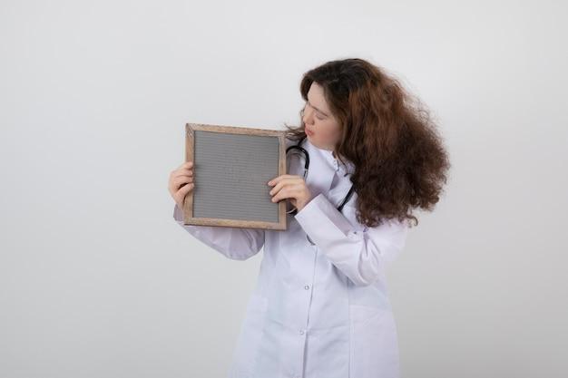 Garota jovem modelo em uniforme branco, segurando uma moldura.