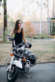 Garota jovem motociclista linda em uma camiseta preta e calça de couro em uma motocicleta. o conceito de velocidade e liberdade