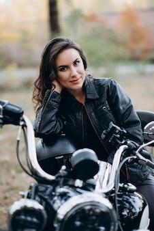 Garota jovem motociclista linda em uma jaqueta de couro preta em uma motocicleta com um capacete nas mãos dele. o conceito de velocidade e liberdade