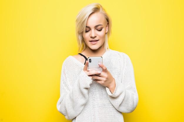 Garota jovem ocupada com suéter branco usa smartphone em amarelo