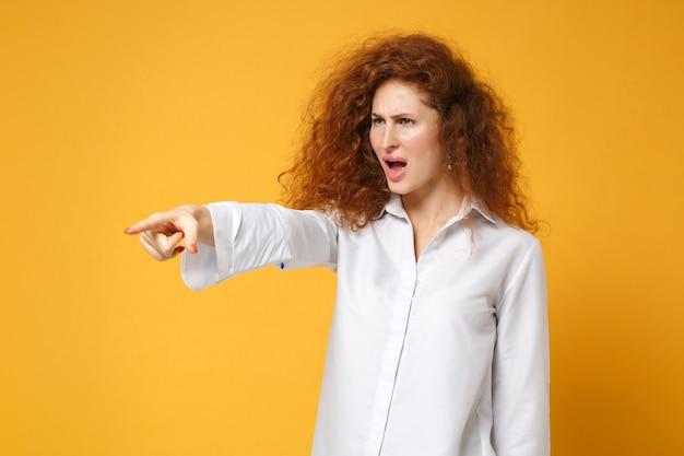 Garota jovem ruiva irritada em uma camisa branca casual posando isolada em uma parede amarelo-laranja