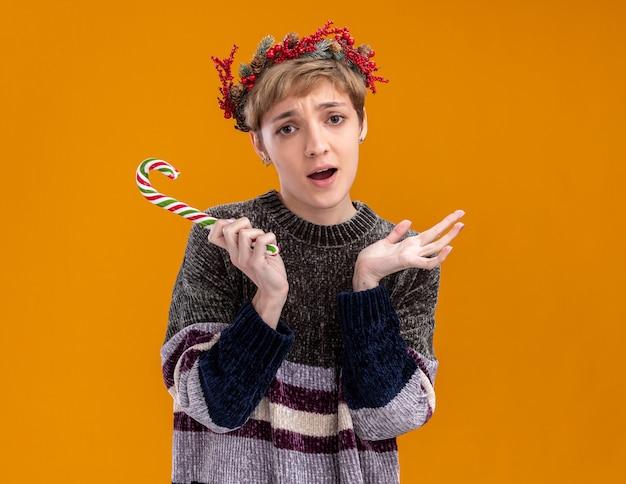 Garota jovem sem noção usando coroa de natal segurando uma cana-doce de natal, olhando para a câmera, mostrando a mão vazia isolada em um fundo laranja