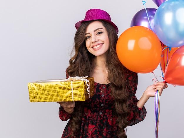 Garota jovem sorridente com chapéu de festa segurando balões e um pacote de presente, olhando para a câmera isolada na parede branca