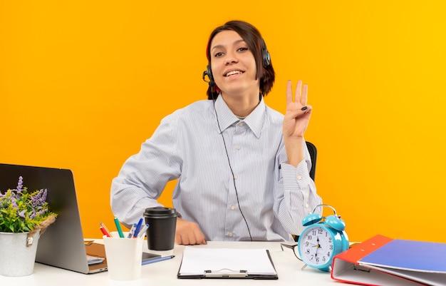 Garota jovem sorridente de call center usando fone de ouvido sentada na mesa, mostrando três com a mão isolada na parede laranja