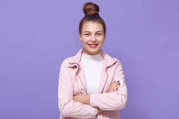 Garota jovem sorridente em uma jaqueta rosa pálida e camisa branca posando isolada na parede lilás, mantendo as mãos cruzadas, feminino, expressando emoções positivas.