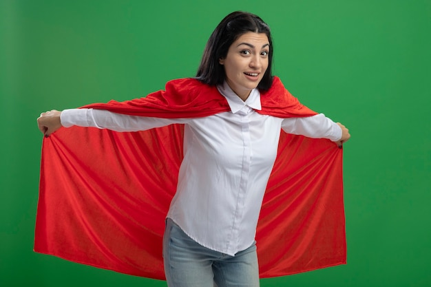 Garota jovem super-heroína caucasiana brincalhona segurando sua capa de herói e representando o voo, olhando para a câmera isolada sobre fundo verde