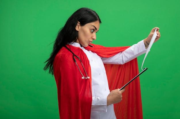 Garota jovem super-heroína surpresa vestindo túnica médica com estetoscópio segurando e virando a prancheta isolada no verde