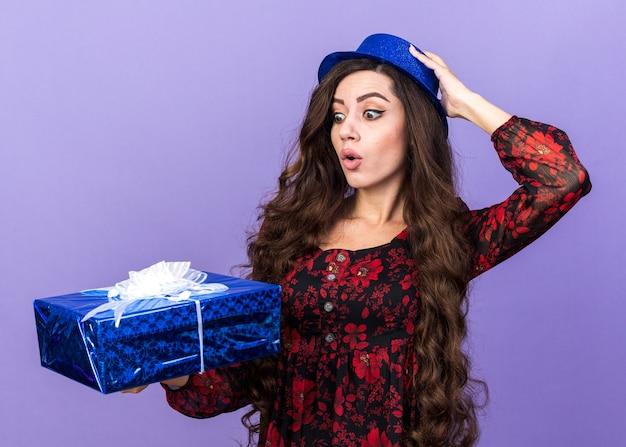 Garota jovem surpresa com chapéu de festa segurando e olhando para um pacote de presente, colocando a mão no chapéu isolado na parede roxa