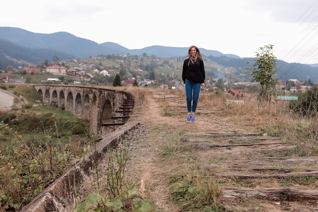 Garota jovem turista caminha pelos velhos trilhos no viaduto.