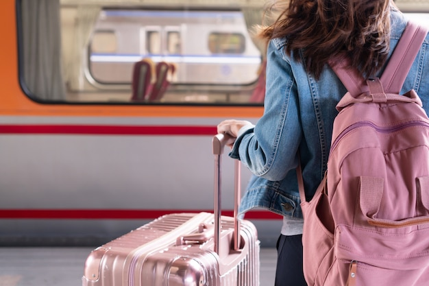 Garota jovem viajante em jaqueta jeans com bolsa rosa e bagagem esperando o trem na plataforma