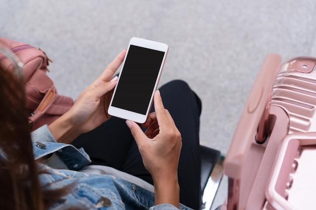 Garota jovem viajante em jaqueta jeans com telefone inteligente, bolsa rosa e bagagem esperando o trem na plataforma, cópia espaço, viagens ou transporte conceito