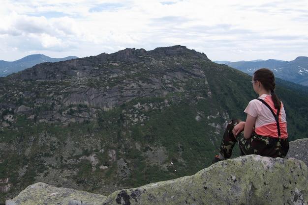 Garota jovem viajante solitária sentada em uma pedra no topo de uma montanha e olhando para as montanhas altas.