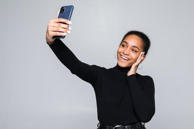 Garota latina, acenando no telefone inteligente enquanto durante uma vídeo chamada isolada