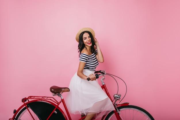 Garota latina animada sentado na bicicleta com um sorriso alegre. retrato de uma senhora elegante com saia exuberante.