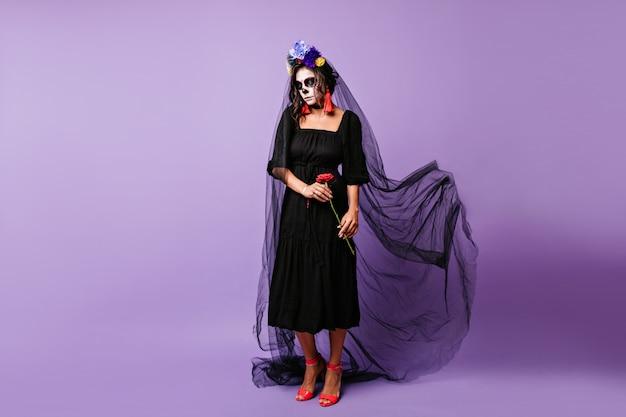 Garota latina atraente posando com véu preto longo no dia dos mortos. mulher vampira encantadora comemorando o dia das bruxas sozinho.