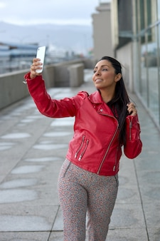 Garota latina com uma jaqueta vermelha tomando uma selfie na rua.