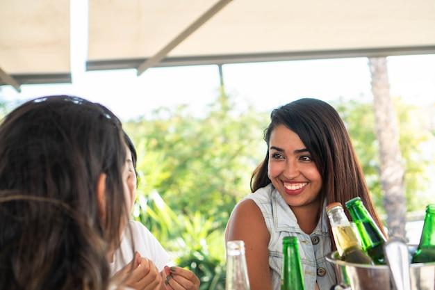 Garota latina conversando com as amigas e tomando algumas cervejas em um dia de sol amigas hispânicas