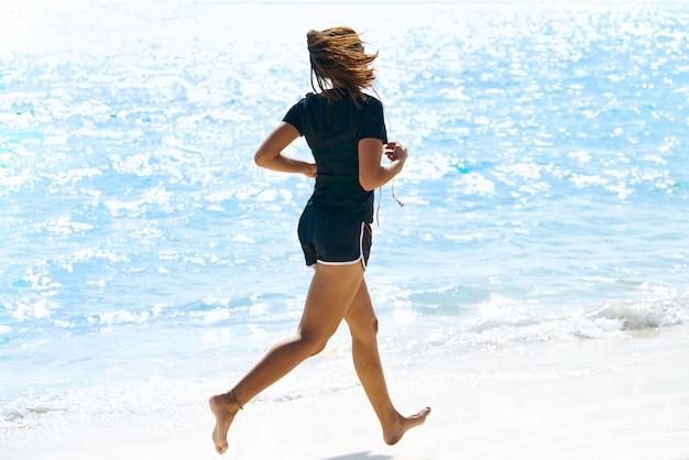 Garota latina correndo na praia do caribe