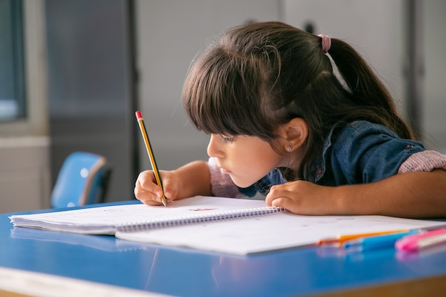 Garota latina de cabelo concentrado sentada na mesa da escola e desenhando em seu caderno