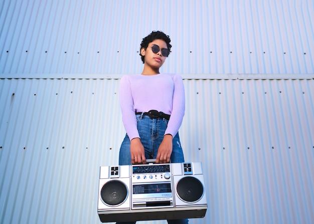 Garota latina mantendo o boombox isolado na parede de chapa cinza