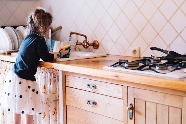 Garota lavando o copo na pia da cozinha