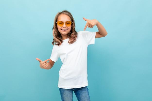 Garota legal adolescente caucasiano em t-shirt branca, óculos amarelos sorri e mostra-se isolado em fundo azul