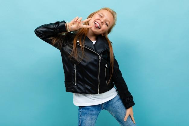 Garota legal adolescente em sorrisos jeans e jaqueta preta isolatedd sobre fundo azul