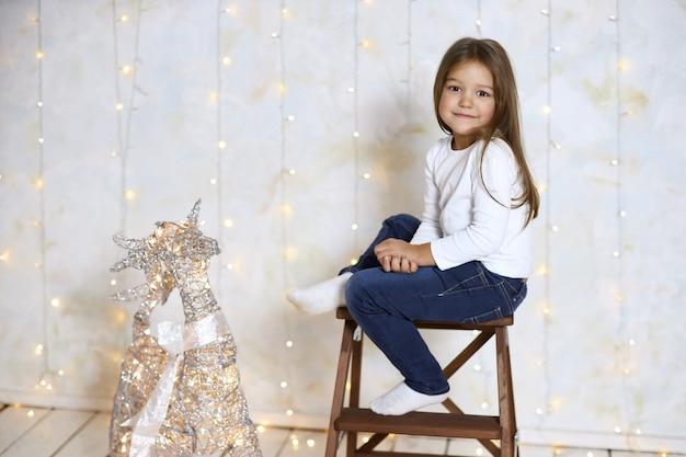 Garota legal com cabelo lon g senta-se na cadeira alta contra uma parede de luz, copie o espaço