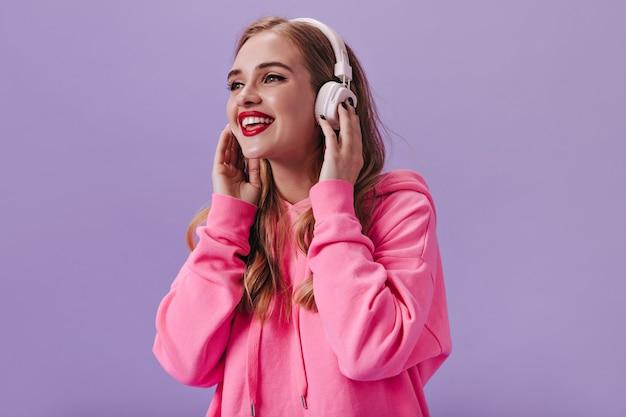 Garota legal com capuz rosa ouvindo música com fones de ouvido brancos