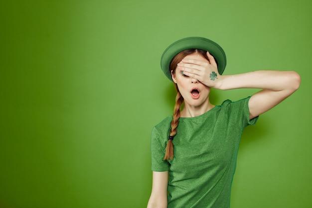 Garota legal com um trevo na mão em um chapéu divertido do dia de são patrício nas férias verdes