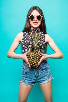 Garota legal do retrato da moda em óculos de sol e abacaxi