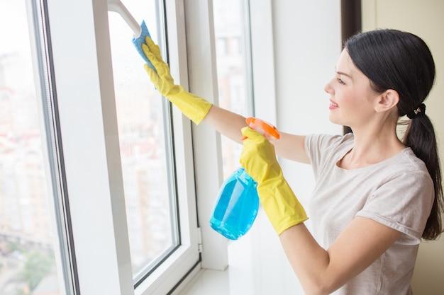 Garota legal e agradável fica na frente da janela e limpá-lo com pano e spray líquido azul. menina usa luvas amarelas.